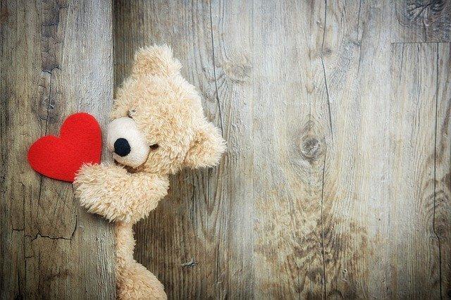 medvídek Teddy se srdcem u dřevěné stěny