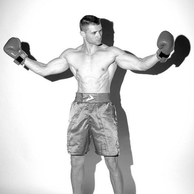muž s boxerskými rukavicemi u zdi